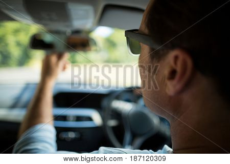 Close up of man adjusting rearview mirror in car