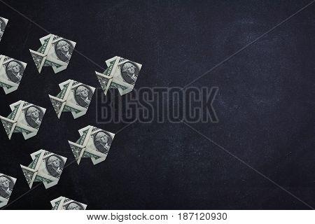 Origami dollar fishs money symbol business on a blackboard background