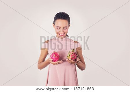 Girl holding up two pink pitaya fruit with both hands facing camera
