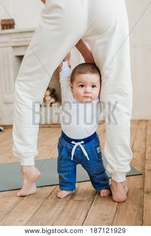 Cropped Shot Of Adorable Baby Boy Standing Between Mother's Legs