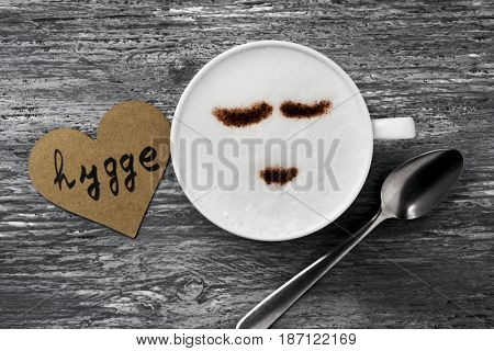 high-angle shot of a cup of cappuccino with a happy face drawn with cocoa powder and a signboard with the text hygge, a danish and norwegian word for comfort or enjoy, a whole philosophy of life