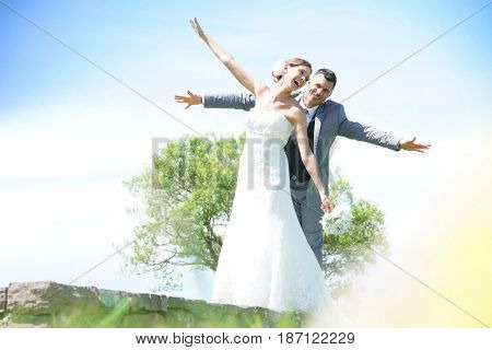 Bride and groom having fun walking in parapet