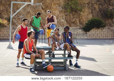 Basketball players sitting on the bench in basketball court outdoors