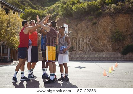 Basketball players giving high five to each other in basketball court outdoors