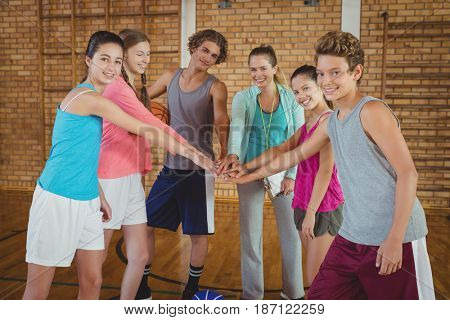 Female coach and high school kids with their hands stacked in basketball court