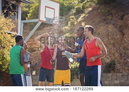 Basketball players celebrating by splashing water on each other in basketball court outdoors