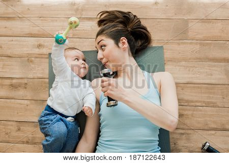 Top View Of Mother With Baby Boy Lying On Floor And Playing With Dumbbells