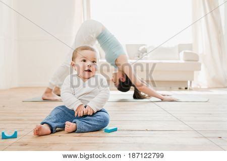 Young Woman In Downward Dog Position While Her Baby Playing At Home