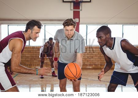 Basketball players ready for the jump ball in the court indoors