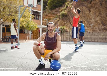 Portrait of basketball player with basketball sitting in basketball court