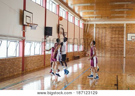 Basketball players playing basketball in the court indoors