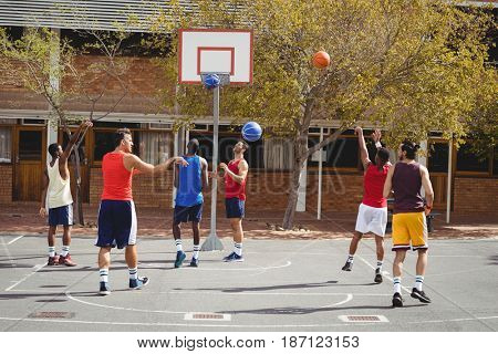 Basketball players practicing in basketball court outdoors