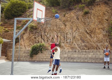 Basketball players playing practicing in basketball court outdoors
