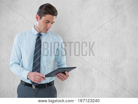 Digital composite of Young businessman holding digital tablet against wall