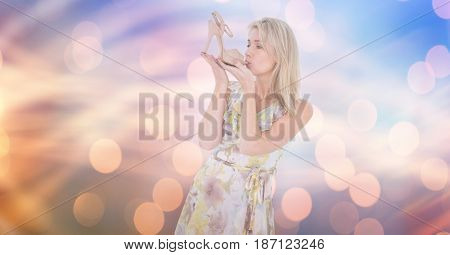 Digital composite of Young woman kissing footwear over bokeh