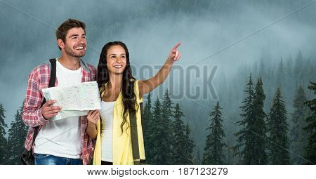 Digital composite of Woman pointing while man holding map during traveling on mountain in foggy weather
