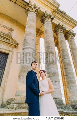 The down view of the newlywed couple looking up while standing near the old building