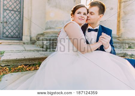 Romantic close-up portrait of the newlyweds sitting on the stairs. The groom is kissing bride in the cheek