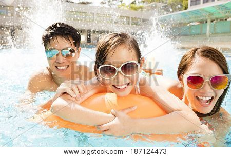 Happy asian family playing in swimming pool