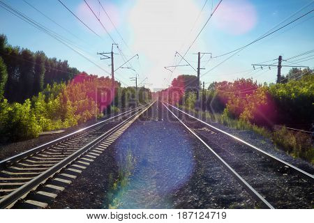 Two railways symmetrically receding to the horizon. Perspective view of railroad at he evening. Soft focus, lens flare.