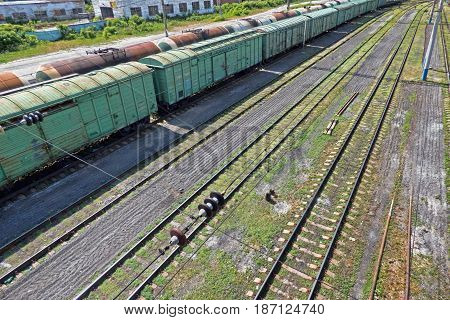 Two long cargo trains and empty railways at station. High angle view.