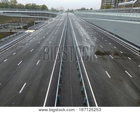 Empty gray highway, outgoing to the horizon. Cloudy rainy day. High buildings in the background. City landscape. Soft focus.