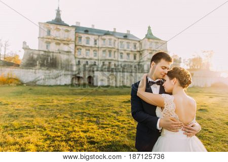 The sensitive close-up outdoor portrait of the groom hugging the bride at the background of the magnificent castle during the sunset. The back view of the bride with bare shoulders