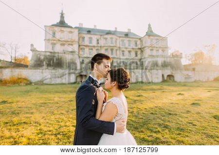 The horizontal side portrait of the happy newlyweds at the background of the old palace. The groom is kissing the bride in the forehead during the sunset