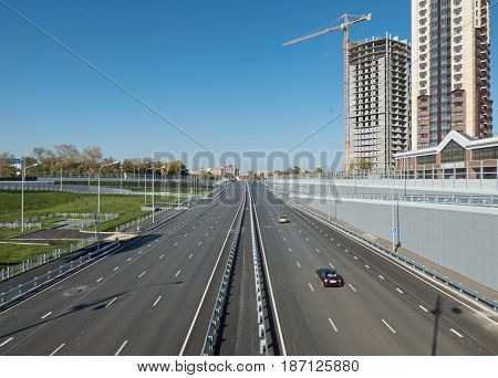 Highway outgoing to the horizon, some cars at the right. Sunny autumn day. High buildings in the background. City landscape with with place for text (on the sky). Soft focus.