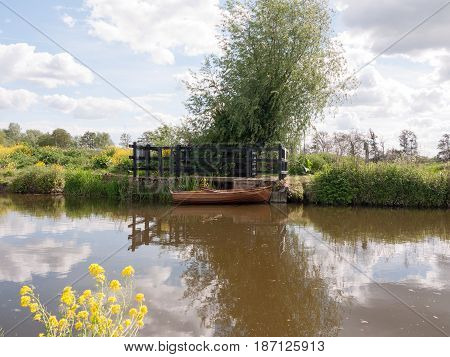A Wooden Boat Moored And Parked On A River In The Countryside Of Essex In The Uk And England With No
