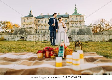 Romantic picnic in the garden of the gothic castle between newlyweds looking at the left side