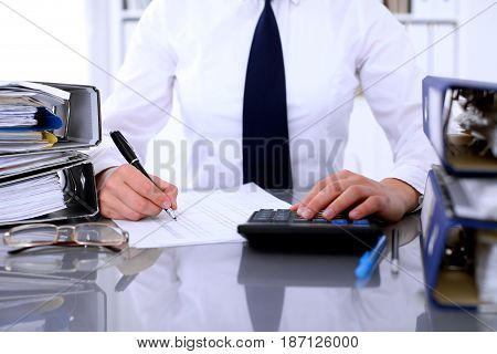 Bookkeeper or female financial inspector  making report, calculating or checking balance. Internal Revenue Service checking financial document. Audit concept.