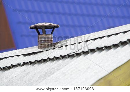 steel flue pipe for the stove with a tip of the hat is mounted on a metal corrugated roof against a blue tiled roofs