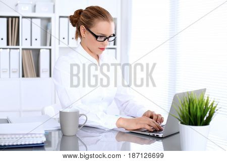 Business woman is typing on laptop computer. Bookkeeper or female financial inspector  making report, calculating or checking balance.