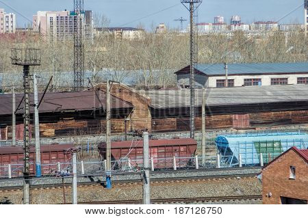 TYUMEN, RUSSIA - 22 APRIL 2017: Railway station Tyumen with cargo train and Warehouse buildings. Spring sunny day. Industrial landscape with wagons, storage and electric poles.