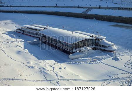 Winter river, empty frozen ships in ice. Lot of people traces around. Siberia, Russia.