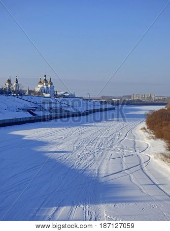 Frozen river in Siberia, Russia. Lot of ski traces in the snow. Two churches and city at the horizon.
