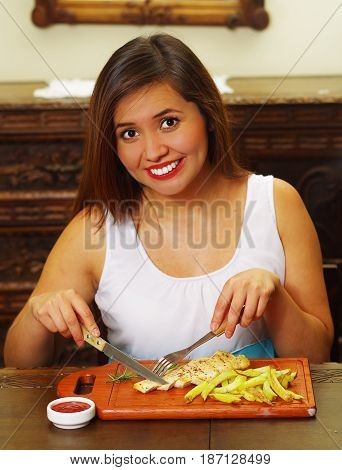 Beautiful smiling girl eating a delicious grilled chicken breast with a small piece of romero spice and ketchup sauce on wooden board.