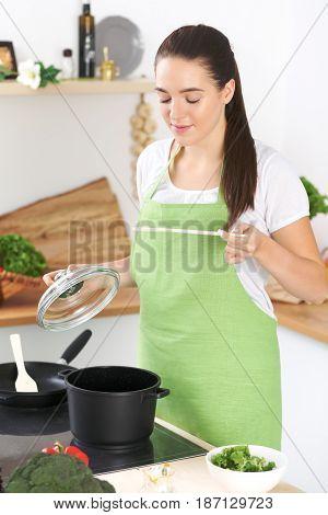 Young caucasian woman in a green apron cooking in the kitchen. Housewife found a new recipe for her soup. Food and health concept.