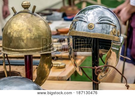 Roman combat helmets exposed at an antique arms exhibition.