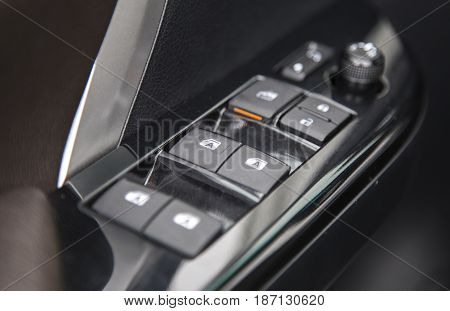 Car interior details of door handle panel with windows controls and adjustments