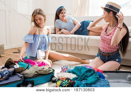 Young Women Packing Suitcases For Vacation Together At Home, Getting Ready To Travel Concept