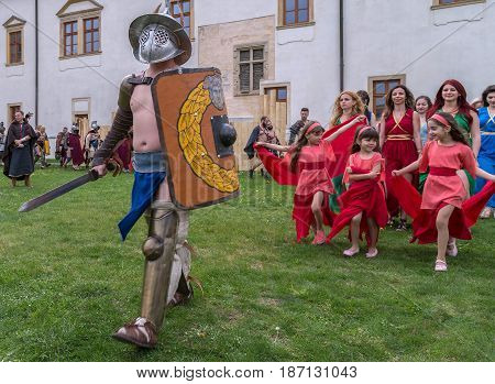 ALBA IULIA ROMANIA - APRIL 29 2017: Roman gladiator in battle costume and a group of young Roman girls at APULUM ROMAN FESTIVAL organized by the City Hall.