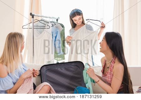 Beautiful Young Women Choosing Clothes And Packing Suitcase For Travel, Packing Luggage Concept