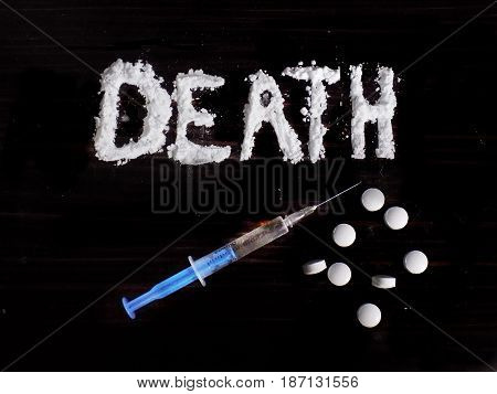 Cocaine drug powder in death word shaped, pills and injection syringe on black background