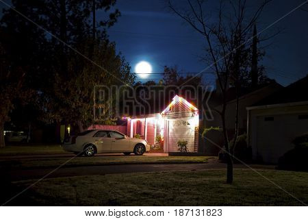 SACRAMENTO, CALIFORNIA, USA -  November 30, 2009: Moon shines above a house decorated with Christmas lights