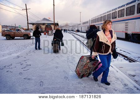 KLAMATH FALLS, OREGON, USA - February 25, 2012: Passenger rolling her luggage towards an Amtrak train while others disembark in snowy weather
