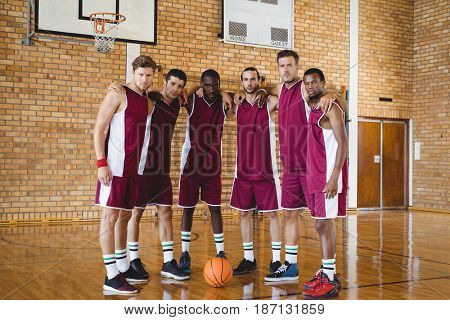 Portrait of confident basketball players standing with arms around in the court