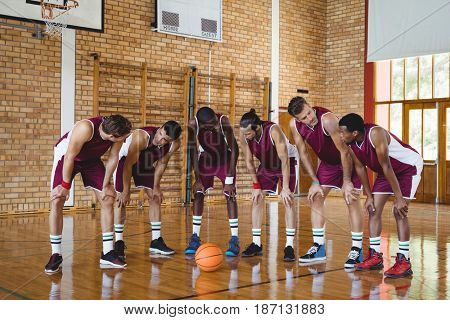 Exhausted basketball players taking a break on basketball court
