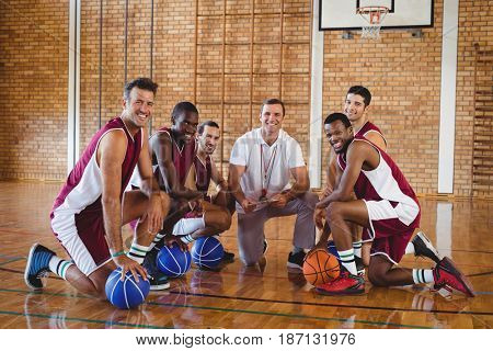 Portrait of smiling coach and players kneeling with basketball in the court